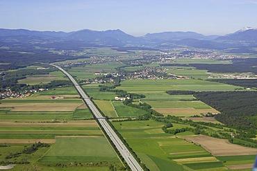 Aerial shot of the South freeway (A2) over the town Neunkirchen to the Rax mountain range, Foehrenau, Lower Austria, Austria