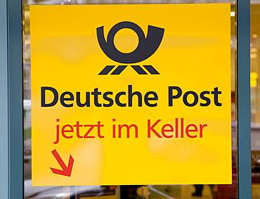 Sign marked with: Deutsche Post jetzt im Keller, Germany
