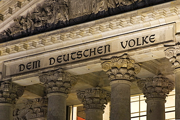 """""""Dem Deutschen Volke"""" (""""To the German people"""") inscribed over the entrance of the Reichstag (German parliament) building by night, Berlin, Germany"""
