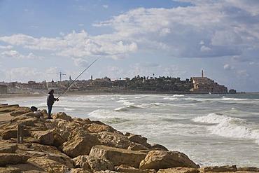 Fisherman fishing on the Tel Aviv shoreline, view toward Jaffa, Israel, Middle East