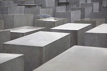 Umbrella amid the stelae or concrete slabs of the Memorial to the Murdered Jews of Europe, Holocaust Memorial, Berlin, Germany, Europe