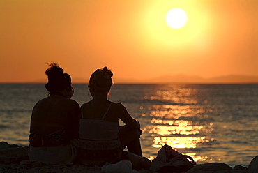 Two women on a beach watching the sunset over the ocean