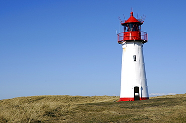 Lighthouse painted red a white standing on grassy hill, Ellenbogen, Sylt Island, North Frisian Islands, Schleswig-Holstein, Germany