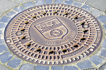 Manhole cover showing the List on Sylt coat of arms, List, Sylt Island, North Frisian Islands, Schleswig-Holstein, Germany