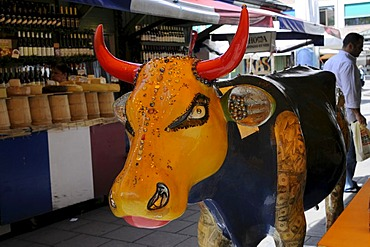 Art object cow in the victualers market, behind it a cheesestand, Munich, Bavaria, Germany, Europe