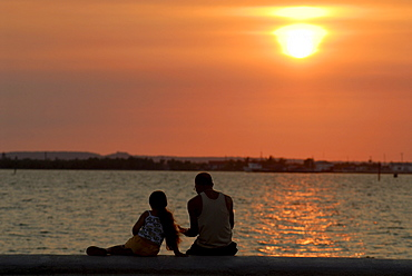 Man and child sitting on the malecon at sunset, Cienfuegos, Cuba, Americas