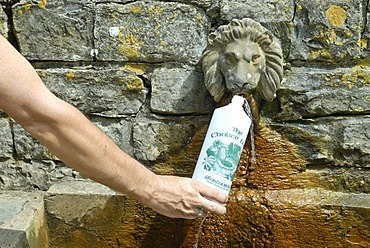 Man filling a bottle of water from Chalice Well, Ley lines, Legend of King Arthur, Glastonbury, Mendip, Somerset, England, Great Britain, Europe