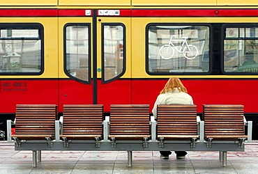 Woman sits in front of tram, Germany