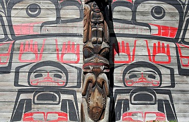 Totem pole in front of a long house at Ksan Historical Village, British Columbia, Canada