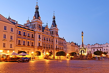 Ornate facade of buildings under streetlights at twilight surrounding the cobbled town square in the historic centre of Pardubice, Pardubice, East Bohemia, Czech Republic, Czechia, Europe