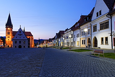 Historic town square of Bardejov surrounded by park benches, glowing street lamps, a church and old renovated terraced buildings, UNESCO World Heritage Site, Slovakia, Europe