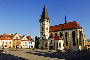 Historic town square of Bardejov surrounded by park benches, a church and old renovated terraced buildings, a UNESCO World Heritage Site, Slovakia, Europe