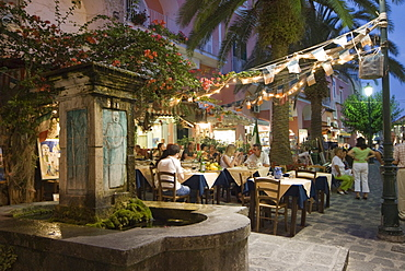 Fountain, restaurant in an alley in the historic centre at dusk, Ischia Ponte, Ischia Island, Campania, South Italy, Europe