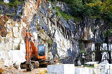 Mechanical shovel excavator in the marble stone pit of Carrara Tuscany Italy