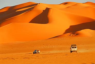Jeeps in front of sand dunes, Murzuq desert, Libya