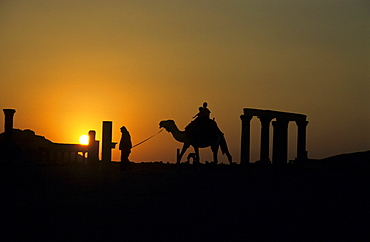Tourist riding a camel at sunset, Palmyra, Syria, Middle East