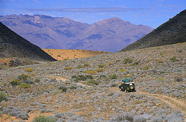 Land Rover in stony desert landscape, Brandberg Mountain backdrop, near Uis, Namibia, Africa