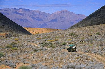 Land Rover in stony desert landscape, Brandberg Mountain backdrop, near Uis, Namibia, Africa