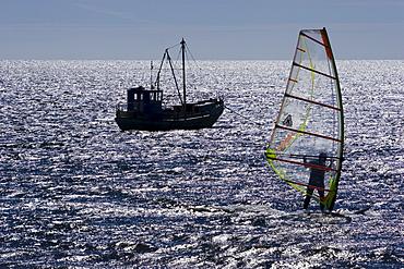 Fishing boat and windsurfer off the coast of Saaremaa Island, Estonia, Europe