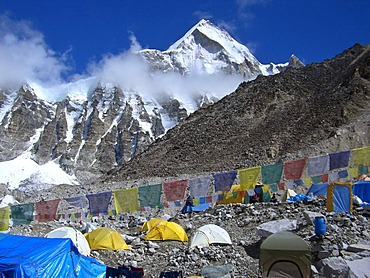 Tibetan praying flags between the tents in the Base Camp, 5300m, in the back the summit of Mount Lingtren, 6600m, Mount Everest, Himalaya, Nepal