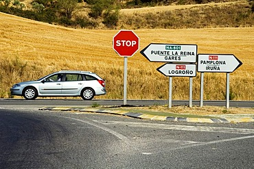 A Renault Laguna estate car is driving past a well signposted crossing, Navarra, Spain