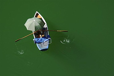 Fisherboat with umbrella in the green Sylvenstein Reservoir, Bavaria, Germany