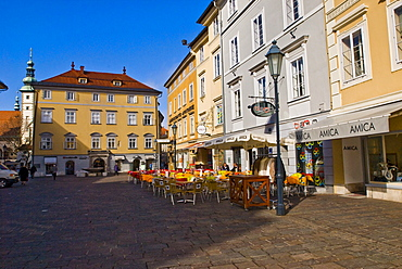 Outdoor cafe on the cobbled old town square surrounded by beautiful old buildings and ornate street lamps in Klagenfurt, Carinthia, Austria