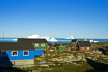 Wooden harbour houses in front of icebergs, Qeqertarsuaq, Disko Island, Disko Bay, Greenland, Arctic