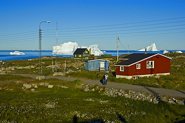Inuit in front of a wooden house, icebergs visible at back, Qeqertarsuaq, Disko Island, Disko Bay, Greenland, Arctic