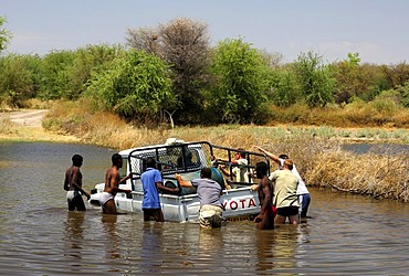 Four-wheel drive jeep booged down while crossing a river, teamwork, Botswana, Africa