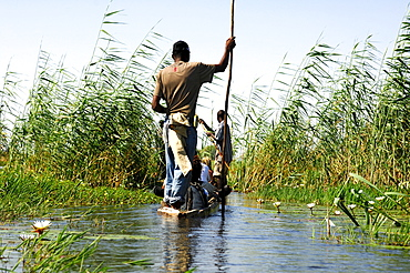 Locals in Mokoro dugoutboat on a tourist excursion in the Okavango Delta, Botswana