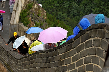 Crowds of tourists push forward on the Chinese Great Wall on a rainy day, China