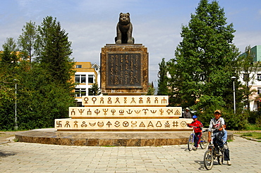 Children cycling past the monument to the Mongolian State Seal, sculpture of a tiger, writing in old Mongolian script, Ulaanbator, Mongolia