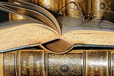 Reading glasses resting on an open page of an old encyclopaedia, leather bound books