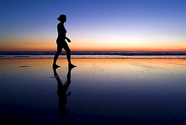 Silhouette of a woman at the beach at sunset, Cable Beach, Australia