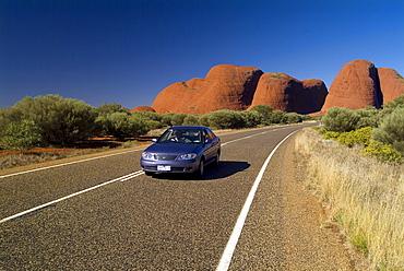 PKW driving on a street in Uluru - Kata Tjuta National Park, Northern Territory, Australia