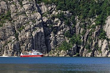 Ship navigating along rock face, Lysefjord, Rogaland, Norway