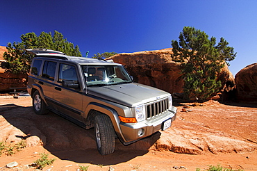 Off-road vehicle Jeep Comander on rocky terrain, Canyonlands, Utah, USA