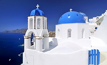 Blue and white domed church and bell tower in front of the blue sea, Oia, Ia, Santorini, Cyclades, Greece, Europe
