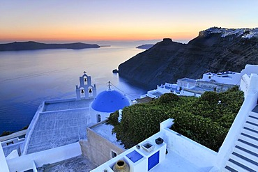 Stairway leading down to a white Greek church with a blue dome and a bell tower at sunset, Firostefani, Santorini, Cyclades, Greece, Europe