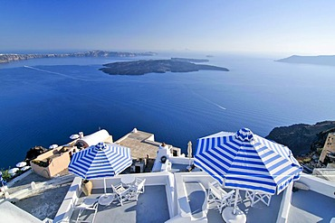 Terraces with blue and white striped sunshades in front of the blue sea and the volcanic island of Nea Kameni, Santorini, Cyclades, Greece, Europe