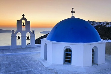White Greek church with a blue dome and a bell tower at sunset, Firostefani, Santorini, Cyclades, Greece, Europe