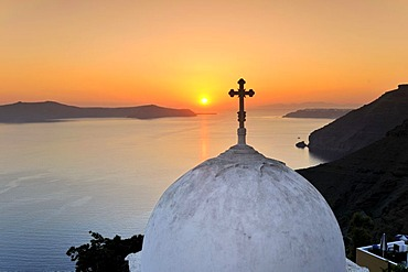 Dome of a church with a cross in front of the sea at sunset, Thira, Fira, Santorini, Cyclades, Greece, Europe