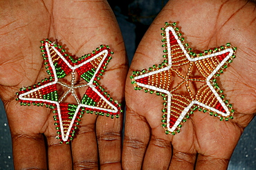 Hands with Christmas stars made of glass beads, Cape Town, South Africa