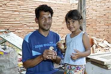 Guarani father and daughter with fledgling in his hand, in the poor area of Chacarita, Asuncion, Paraguay, South America