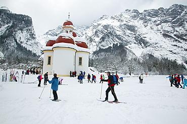 St. Bartholomew's Church at the frozen Koenigssee, cross-country skiers, Berchtesgadener Land, Upper Bavaria, Germany