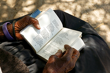Elderly woman turning the pages of a hymnal, Sehitwa, Botswana, Africa