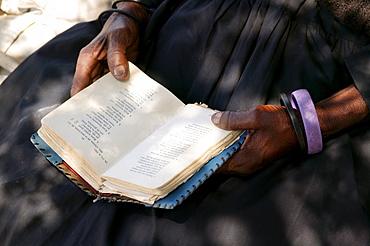 Woman's hands and hymnal, Sehitwa, Botswana, Africa