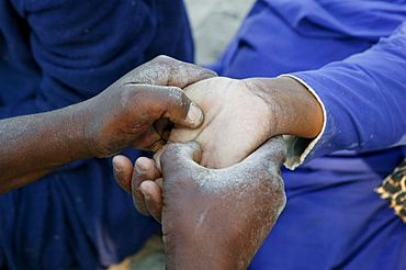 Traditional healer reading the palm of a sick patient, Sehitwa, Botswana, Africa