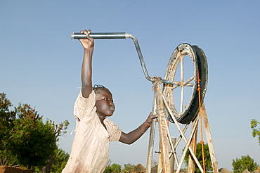 Boy fetching water from a well, Cameroon, Africa